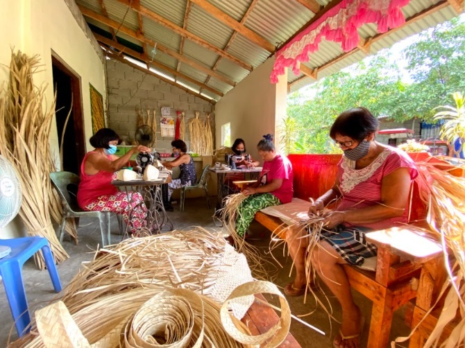 2 Wives of farmers weaving the masks made out of buri palm.
